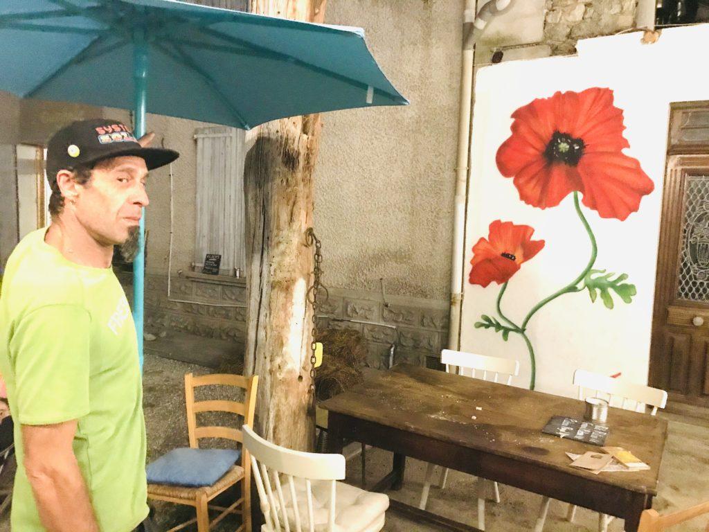 Tof et le début de sa fresque, un coquelicot, sur le mur de la grange.